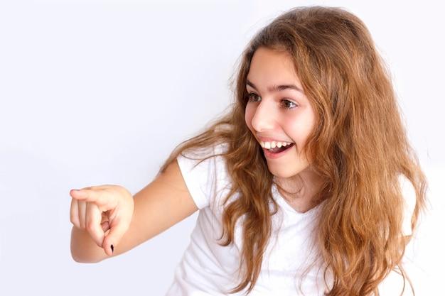 Menina adolescente ri e aponta para algo com um dedo