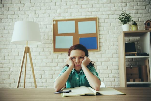 Menina adolescente ruiva está entediada enquanto fazendo lição de casa.