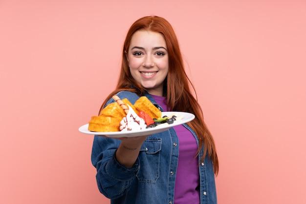 Menina adolescente ruiva segurando waffles sobre parede rosa isolada com expressão feliz