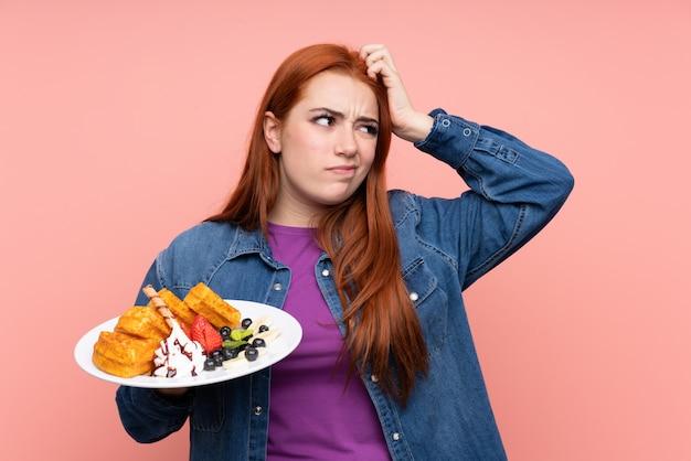 Menina adolescente ruiva segurando waffles sobre parede rosa isolada, tendo dúvidas e com a expressão do rosto confuso