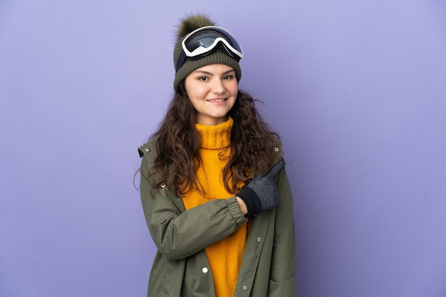 Menina adolescente russa com óculos de snowboard isolados em um fundo roxo apontando para o lado para apresentar um produto