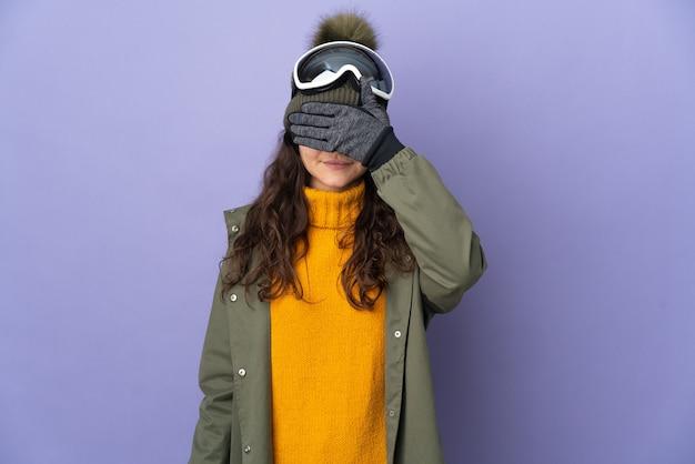 Menina adolescente russa com óculos de snowboard isolados na superfície roxa, cobrindo os olhos com as mãos. não quero ver nada
