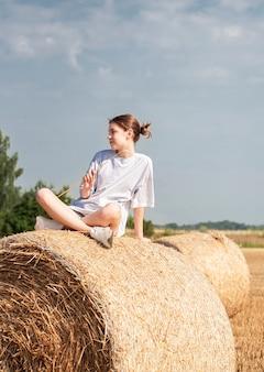 Menina adolescente se divertindo em um campo de trigo em um dia de verão. menina com o fardo de feno durante a época da colheita.