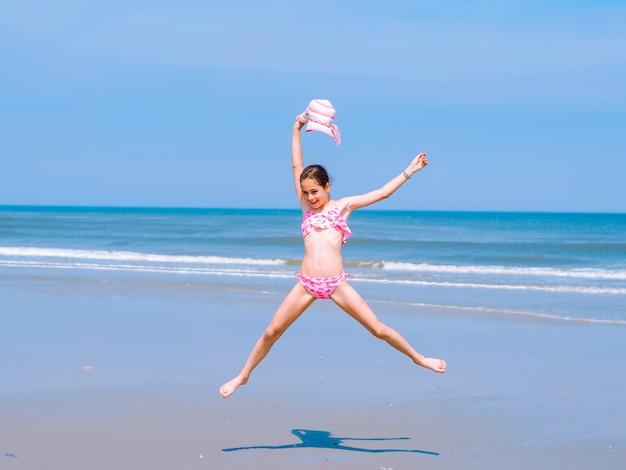 Menina adolescente se divertindo na praia tropical e saltar para o ar na costa do mar