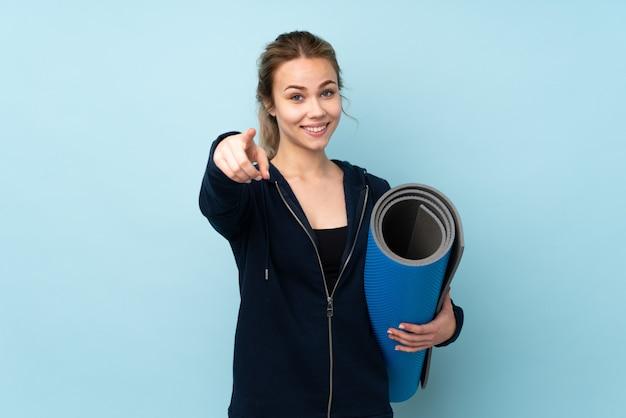 Menina adolescente segurando a esteira em azul fazendo gesto de telefone e apontando a frente