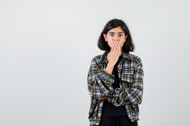Menina adolescente segurando a mão na boca em uma camisa casual e parecendo chocada, vista frontal.
