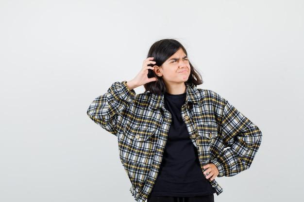 Menina adolescente segurando a mão na cabeça, olhando de lado em uma camisa casual e olhando pensativa, vista frontal.