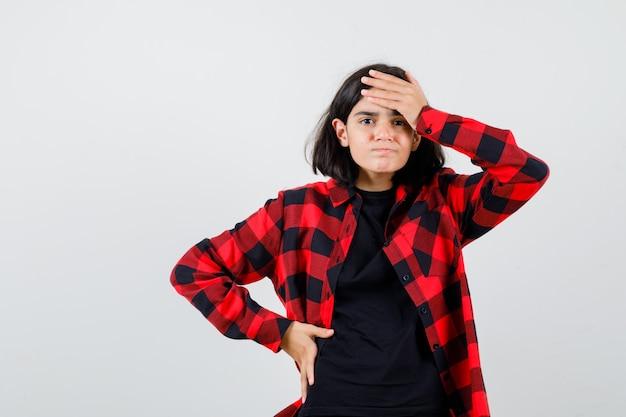 Menina adolescente segurando a mão na testa em t-shirt, camisa quadriculada e parecendo esquecido, vista frontal.