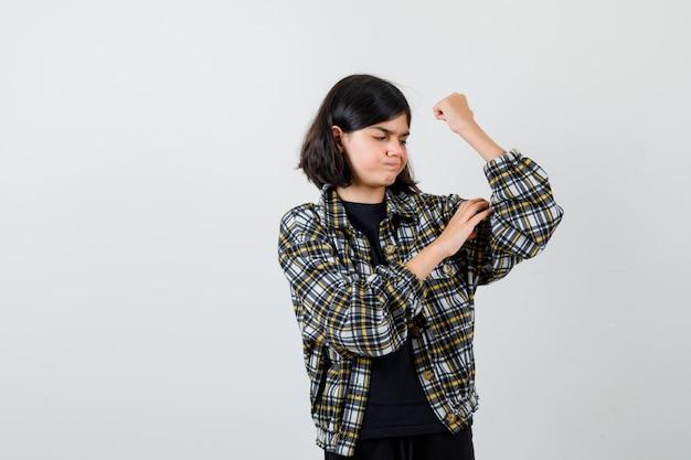 Menina adolescente segurando a mão nos músculos do braço em camisa casual e olhando pensativa. vista frontal.