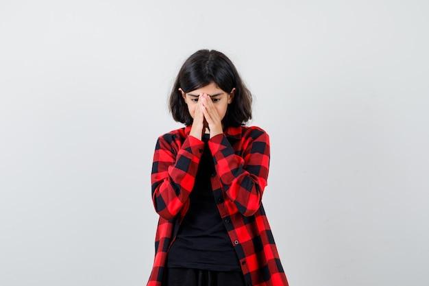 Menina adolescente segurando as mãos no rosto em t-shirt, camisa quadriculada e olhando triste, vista frontal.