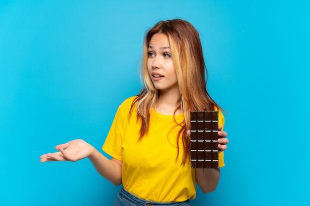 Menina adolescente segurando chocolate sobre fundo azul isolado com expressão de surpresa enquanto olha para o lado