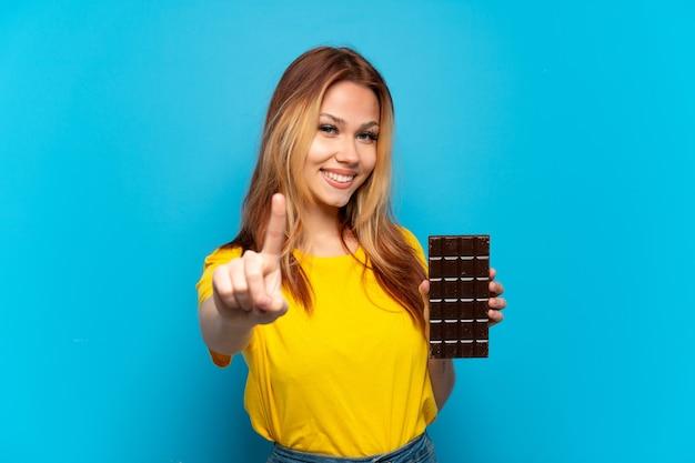 Menina adolescente segurando chocolate sobre fundo azul isolado, mostrando e levantando um dedo