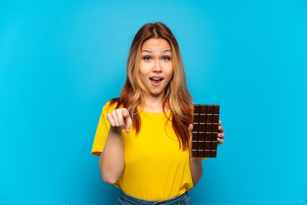 Menina adolescente segurando chocolate sobre fundo azul isolado surpresa e apontando para frente