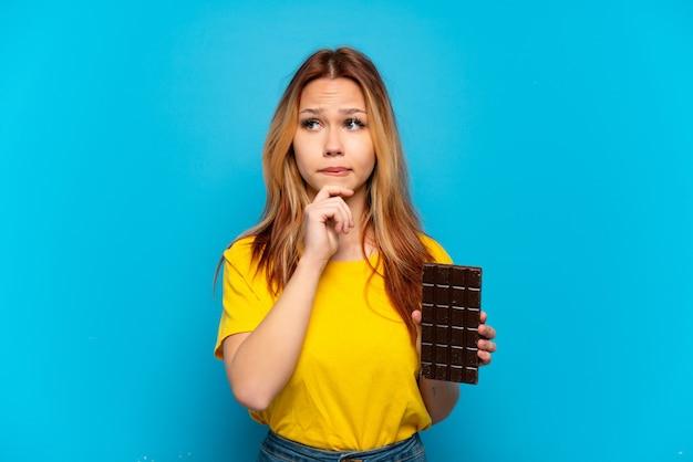 Menina adolescente segurando chocolate sobre fundo azul isolado, tendo dúvidas e pensando