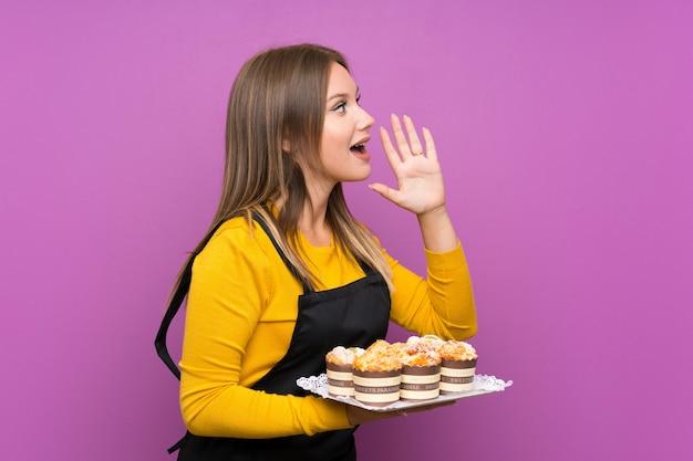 Menina adolescente segurando lotes de diferentes mini bolos roxos gritando com a boca aberta