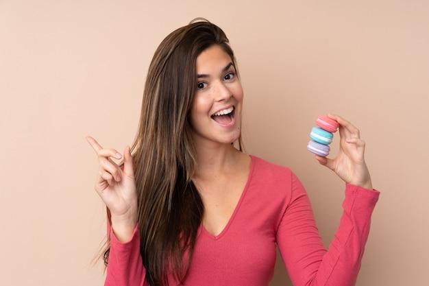 Menina adolescente segurando macarons franceses coloridos e apontando uma ótima idéia