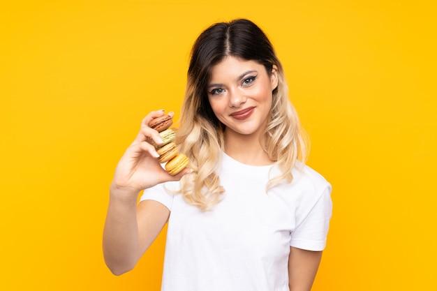 Menina adolescente segurando macarons franceses coloridos e com uma expressão feliz