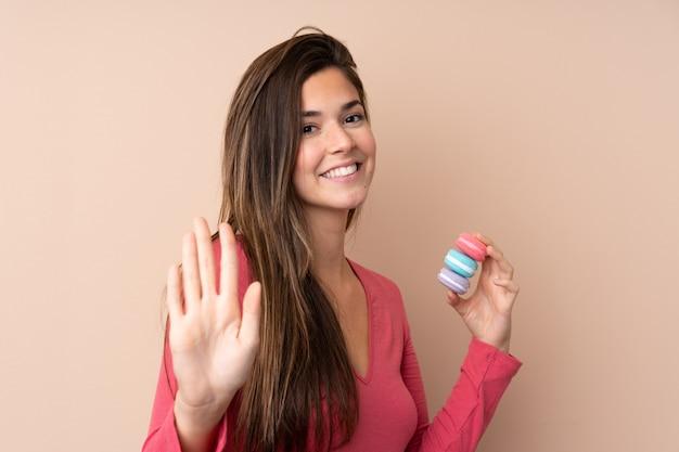 Menina adolescente segurando macarons franceses coloridos e saudação
