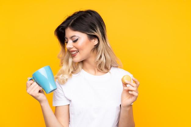 Menina adolescente segurando macarons franceses coloridos e um copo de leite