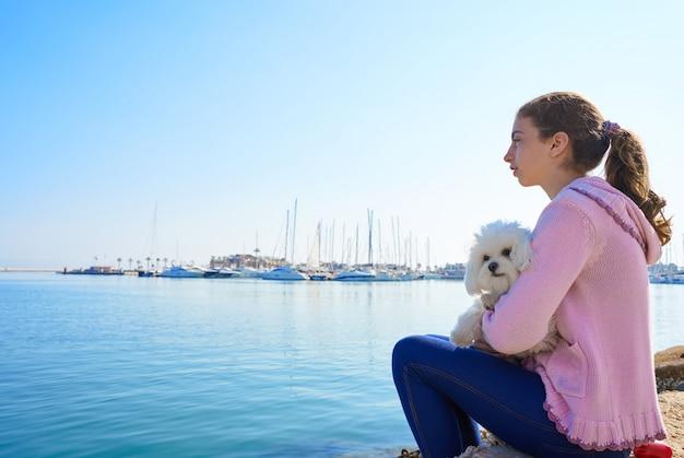 Menina adolescente, segurando, maltichon, cachorro cachorro