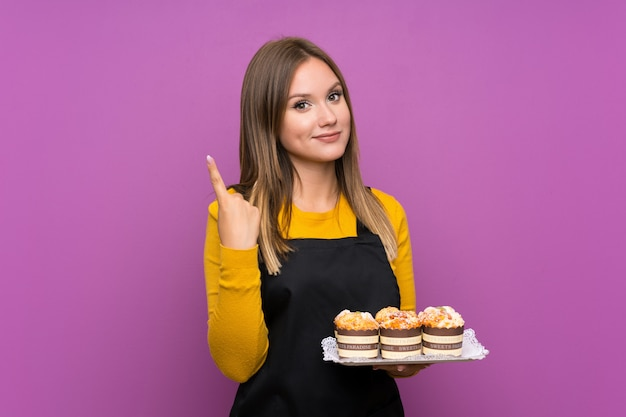 Menina adolescente segurando muitos mini bolos diferentes sobre parede roxa isolada, apontando com o dedo indicador uma ótima idéia