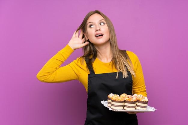 Menina adolescente segurando muitos mini bolos diferentes sobre roxo isolado ouvindo algo