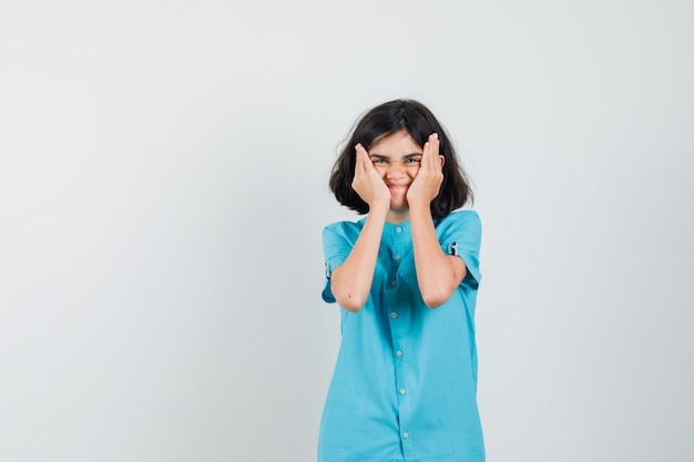 Menina adolescente segurando o rosto com as mãos enquanto sorri com uma camisa azul e parece estranha