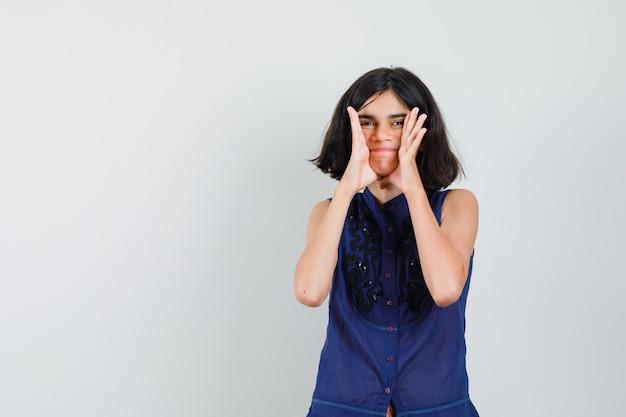 Menina adolescente segurando o rosto com as palmas das mãos abertas na blusa e parecendo estranho.