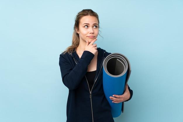 Menina adolescente segurando o tapete na parede azul, tendo dúvidas e com a expressão do rosto confuso