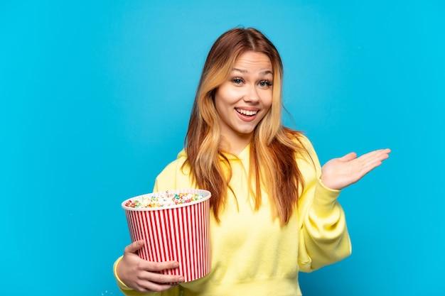 Menina adolescente segurando pipocas sobre um fundo azul isolado com expressão facial chocada