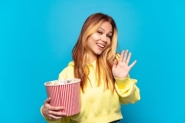 Menina adolescente segurando pipocas sobre um fundo azul isolado e saudando com a mão com uma expressão feliz
