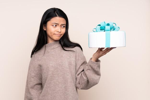 Menina adolescente segurando um bolo grande isolado em bege com expressão triste