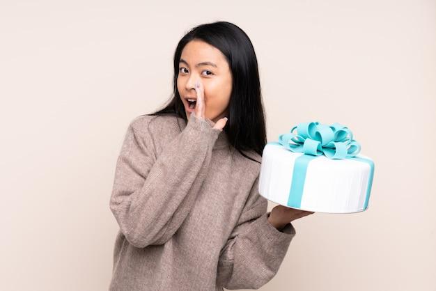 Menina adolescente segurando um bolo grande isolado em bege sussurrando algo