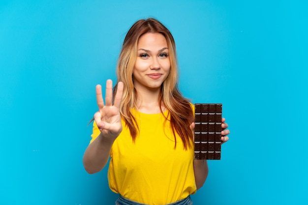 Menina adolescente segurando um chocolate isolado feliz e contando três com os dedos