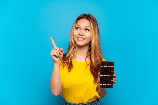 Menina adolescente segurando um chocolate sobre um fundo azul isolado apontando uma ótima ideia