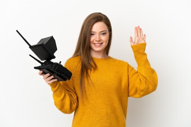 Menina adolescente segurando um controle remoto de drone sobre um fundo branco isolado e saudando com a mão com uma expressão feliz