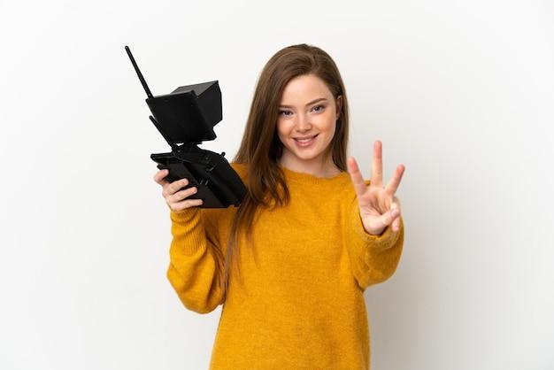 Menina adolescente segurando um controle remoto de drone sobre um fundo branco isolado feliz e contando três com os dedos
