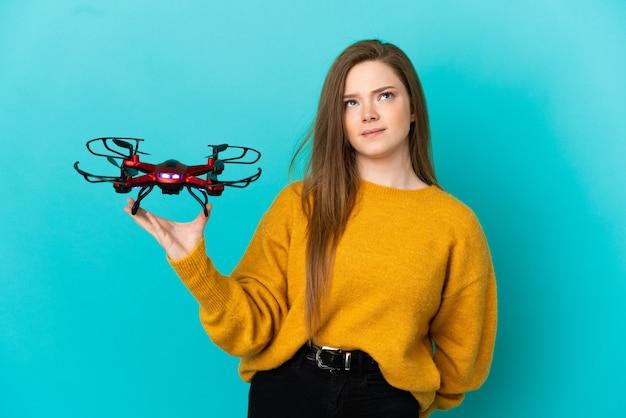Menina adolescente segurando um drone sobre um fundo azul isolado e olhando para cima