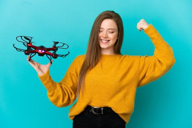 Menina adolescente segurando um drone sobre um fundo azul isolado fazendo um gesto forte