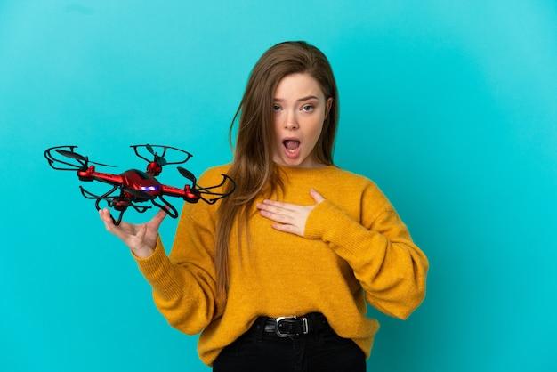 Menina adolescente segurando um drone sobre um fundo azul isolado surpresa e chocada enquanto olha para a direita