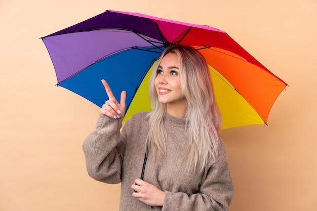 Menina adolescente segurando um guarda-chuva sobre parede apontando com o dedo indicador uma ótima idéia