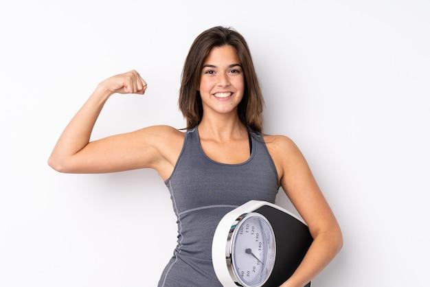 Menina adolescente segurando uma balança sobre parede branca isolada