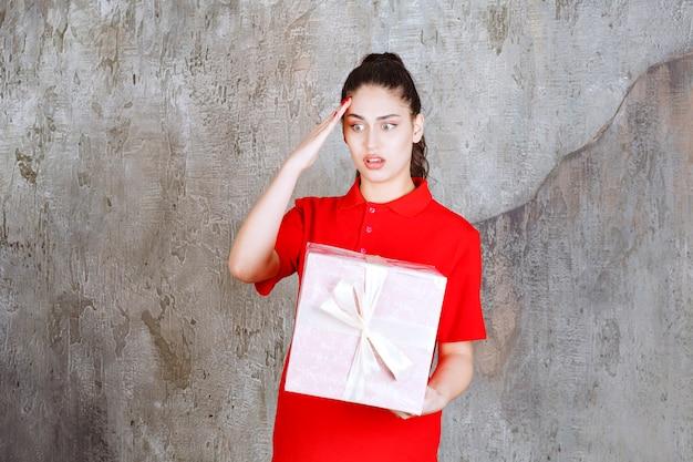 Menina adolescente segurando uma caixa de presente rosa embrulhada com fita branca e parece estressada e nervosa.
