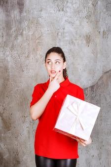 Menina adolescente segurando uma caixa de presente rosa embrulhada com fita branca e parece pensativa.