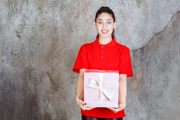 Menina adolescente segurando uma caixa de presente rosa embrulhada com fita branca.