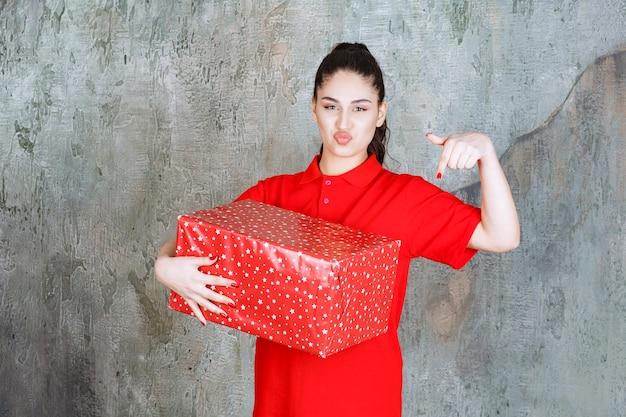 Menina adolescente segurando uma caixa de presente vermelha com pontos brancos e convidando alguém ao lado dela.