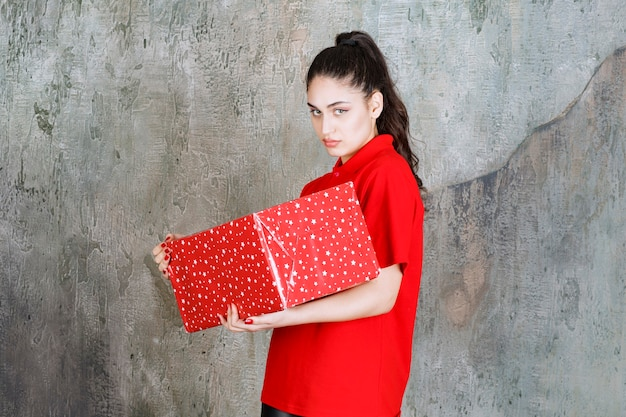 Menina adolescente segurando uma caixa de presente vermelha com pontos brancos, parece insatisfeita e se recusa a fazer algo.