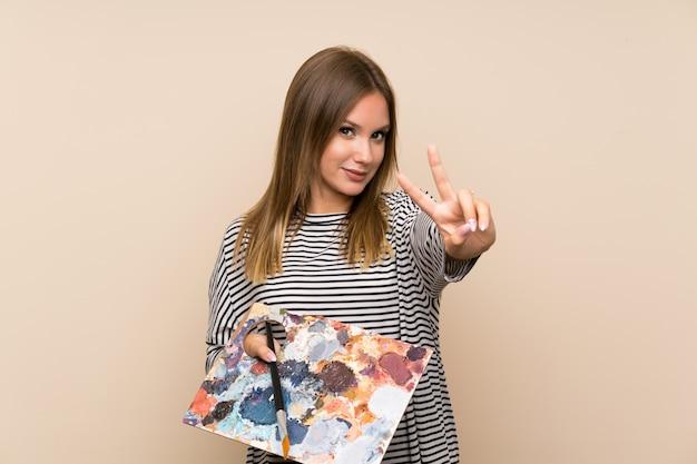 Menina adolescente segurando uma paleta sorrindo e mostrando sinal de vitória