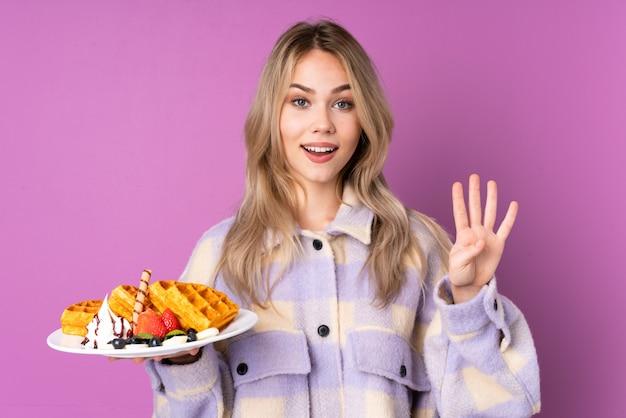 Menina adolescente segurando waffles na parede roxa feliz e contando quatro com os dedos