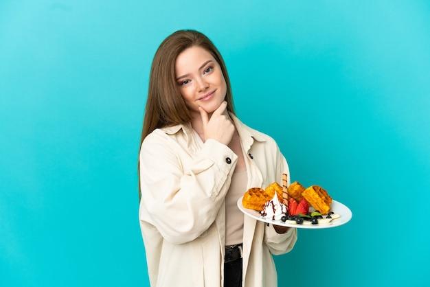 Menina adolescente segurando waffles sobre fundo azul isolado pensando